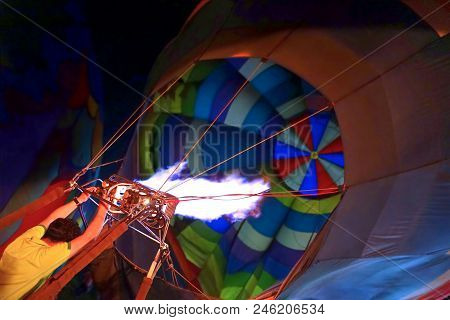 Man Filling The Orange Balloon With Hot Air. View Of The Flame Inside Of A Hot Air Balloon Being Inf