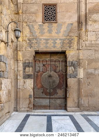 Wooden Decorated Copper Plated Door And Stone Bricks Wall At The Courtyard Of Al-sultan Al-zahir Bar