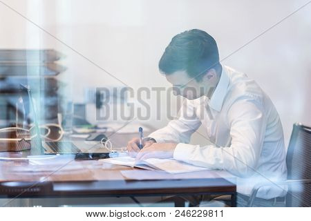 Businessman Working With Documents In The Office. Trough The Window Glass View.