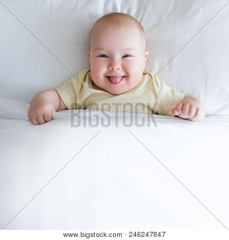 Top View Of Funny Little Baby Lying On The Bed Under White Blanket