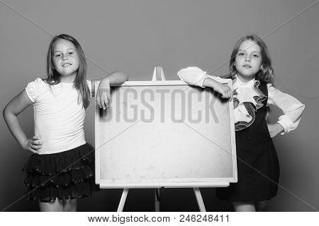 Girls In School Uniform On Blue Background. Education And School Concept. Children Lean On Blackboar