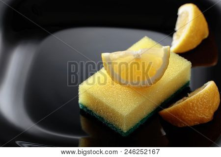 Black plate and dish sponge . Lemon slices . Conceptual image on the theme of purity and freshness . poster