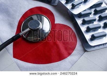 Stethoscope And A Few Blisters Of Pills With Red Heart On White Background. Heart Health Care Medica