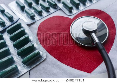 Conceptual Photo That Depicts The Heart Disease. Red Heart, Stethoscope And Bunch Of Blisters With G
