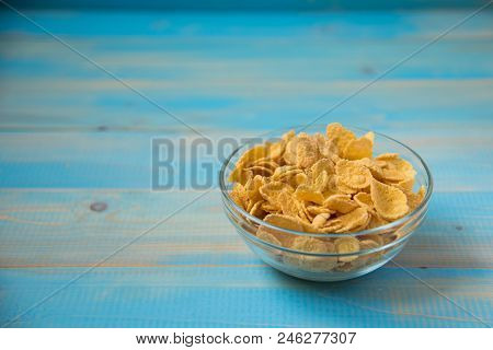 Tasty Cornflakes In Glass Bowl On Blue Background. Healthy Breakfast-cornflakes
