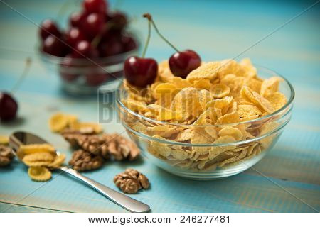 Tasty Cornflakes With Walnut And Cherry In Glass Bowl On Blue Background. Corn Flakes Healthy Breakf