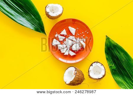 Coconut Pulp On Plate Near Cut Coconut And Palm Leaves On Yellow Background Top View.