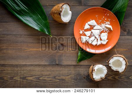 Coconut Pulp On Plate Near Cut Coconut And Palm Leaves On Dark Wooden Background Top View.