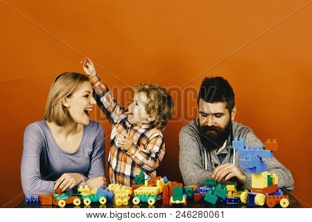 Parents And Kid In Playroom. Family With Cheerful Faces Build Toy Cars Out Of Colored Construction B