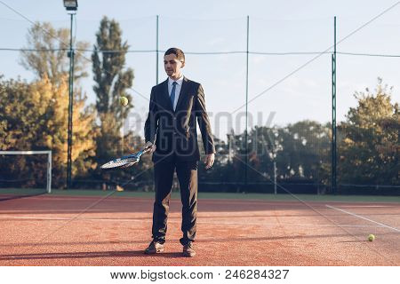 Concept Business And Sport. Smiling Businessman Warming Up Hitting The Ball With Racket, Wearing Sui