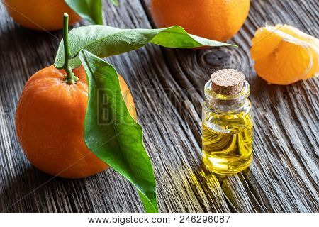 A Bottle Of Citrus Essential Oil With Fresh Tangerines