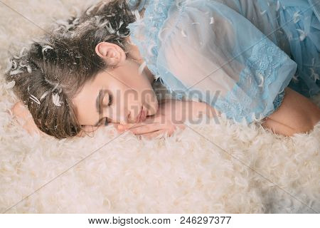 Woman With Long Hair In Tender Pajama Relaxing. Girl On Calm Face Lay On Bed Covered With Feathers A