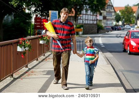 Parent Taking Child, Kid Boy To School. Pupil Of Primary School Go Study. Father Holding Hand Of Lit