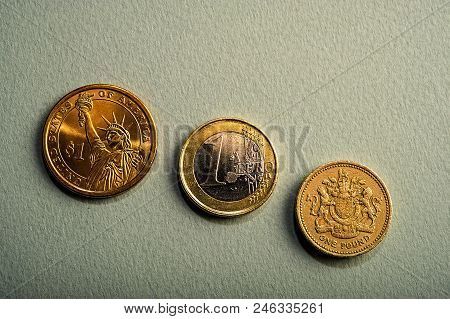 Coins One Dollar, One Euro, One Pound On A Pink Background. Types Of Coins Of America, Europe, Engla