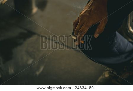 Asian Man With Dirty Hand Hold Cigarette And Smoke. Poor Asian Men Labor Sit And Smoking Cigarette W