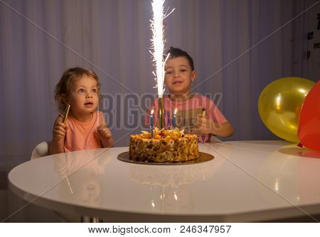 Cute Little Brothers Blowing Out Candles On Birthday Cake At Party Happy