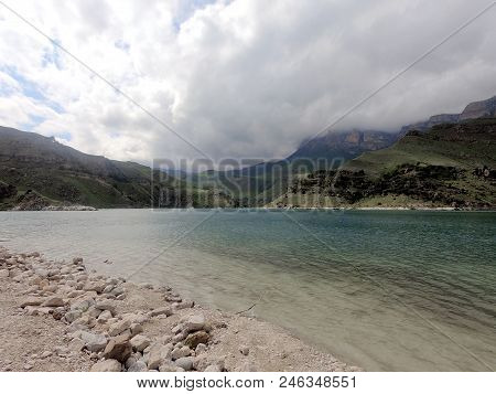 Photo Of The Lake On The Background Of Mountains Of Hills And Rocks, In The Foreground Sandy Beach W