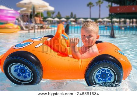 Happy little boy swimming in the inflatable car on summer holidays