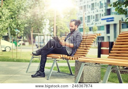 leisure, technology, communication, travel and people concept - man with tablet pc computer sitting on city street bench