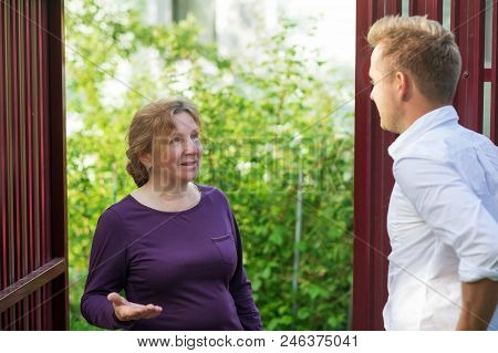Neighbors Discuss The News, Standing At The Fence. An Elderly Woman Talking With A Young Man. They A