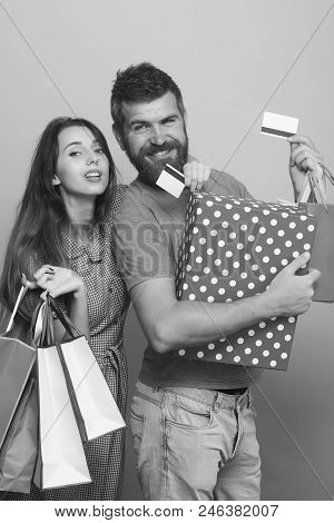 Shopping And Money Spending Concept. Guy With Beard And Pretty Lady Do Shopping. Couple In Love Hugs