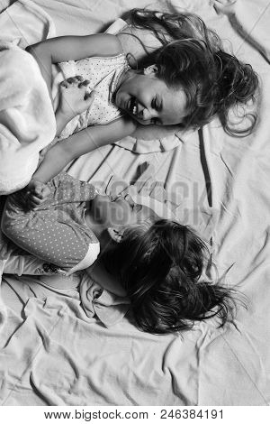 Kids With Happy Faces Have Rest In Bed. Girls Lie On White And Pink Bed Sheets Background Tickling.