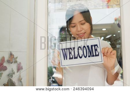 Owner Of Modern Beauty Salon Putting Welcome Notice On The Door