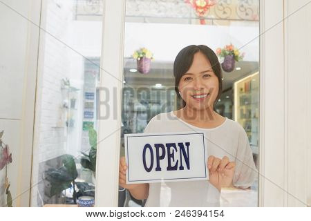 Young Smiling Owner Of Asian Spa Salon Standing By Door And Holding Open Notice