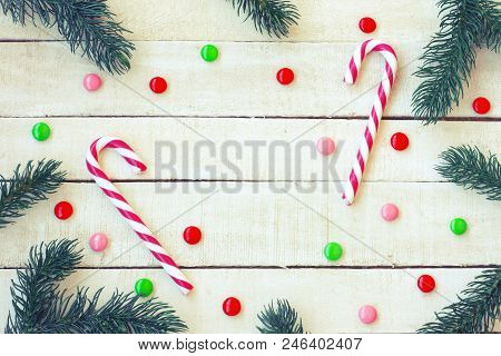 Christmas, New Year Background, Candy, Spruce Branches On White Wooden Table, Top View, Space For Te