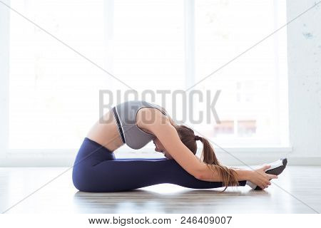 Beautiful Young Woman Working Out Indoors, Doing Yoga Exercise, Does Stretching On The Floor, In The