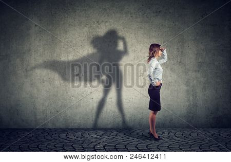 Side View Of A Business Woman Imagining To Be A Super Hero Looking Aspired.