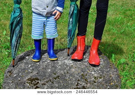 Little Two Years Old Boy And Older Teenage Sister Wearing Rubber Boots Holding Umbrellas And Standin