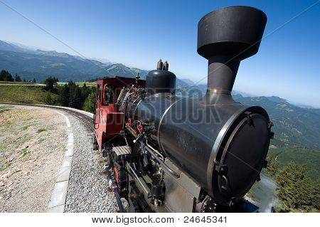 An old steam locomotive is climbing up the 'schafbergbahn' on to the top of the Schafberg (1783 meters) in Austria. poster