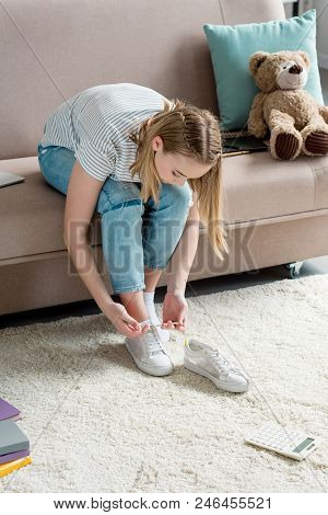 Teen Girl Lacing Up Shoes While Sitting On Couch At Home