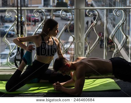 Man And Woman In Sportswear In Gym, Window On Background. Couple Stretching Or Busy With Physical Pr