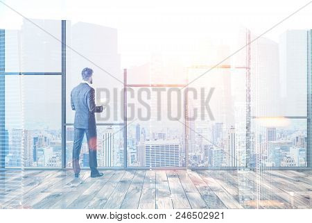 Businessman Standing In A Modern Panoramic Office Empty Room With A Wooden Floor. 3d Rendering Mock