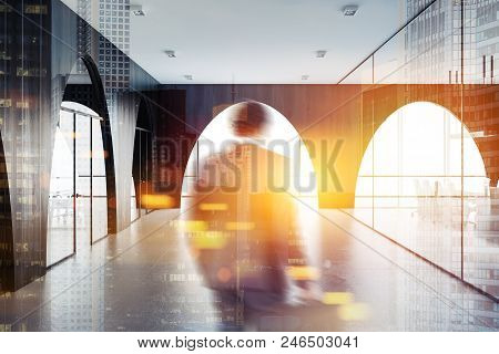 Businessman In Modern Office Lobby With A Concrete Floor, Arched Dark Wooden Walls And Panoramic Win
