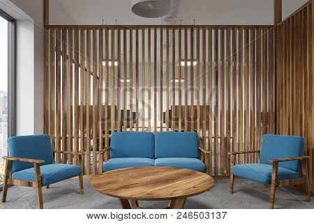 Office Waiting Room Interior With A Round Table, Blue Armchairs And Sofa And Wooden Walls. 3d Render