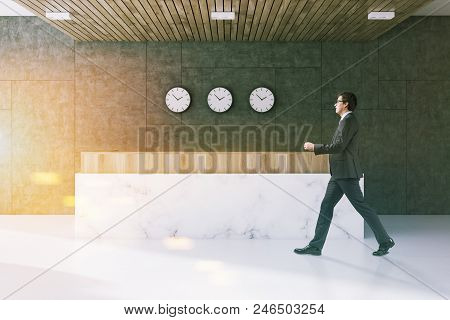 Businessman In A Gray Wall Office Waiting Room Interior With A Marble Floor, And A White Marble And