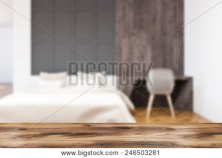 White And Gray Wall Bedroom Interior With A White Bed, A Table With Computer On It And A Wooden Floo