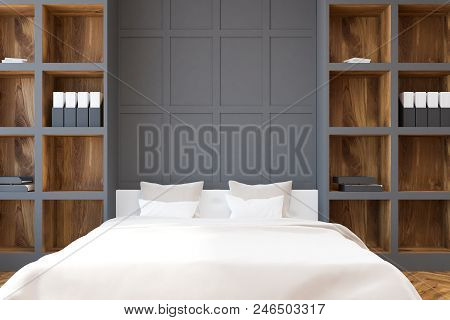Wooden And Gray Wall Bedroom Interior With A White Bed Standing Between Bookcases On A Wooden Floor.