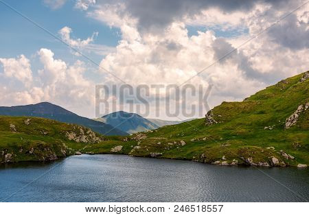 Gorgeous Cloudscape Over The Capra Lake. Amazing Fagaras Mountain Ridge In The Distance.