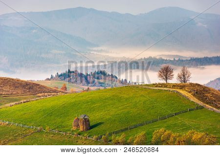 Haystack On Rural Fields In Foggy Mountainous Area. Beautiful Countryside Landscape In Autumn. Fores