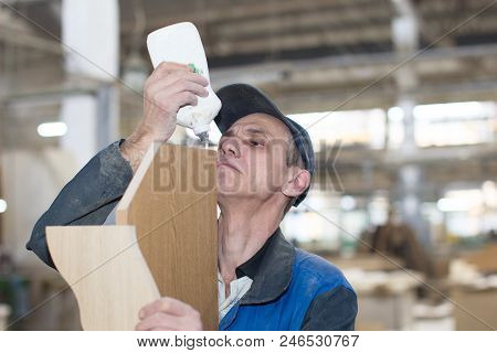 Belarus, The City Of Gomel, On April 26, 2018. Furniture Factory. A Man Working Glues Furniture. To