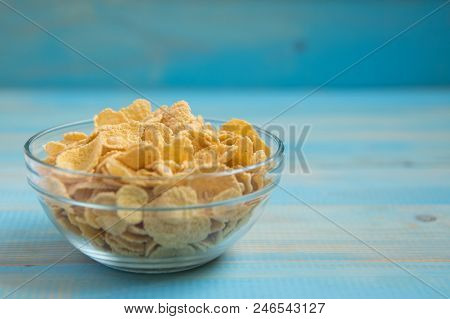 Tasty Cornflakes In Glass Bowl On Blue Background. Healthy Food Background.