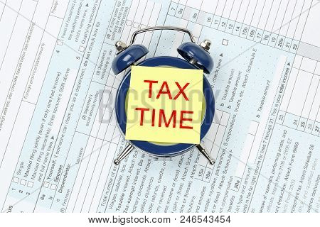 Tax Concept With Yellow Note On Alarm Clock On 1040 Form
