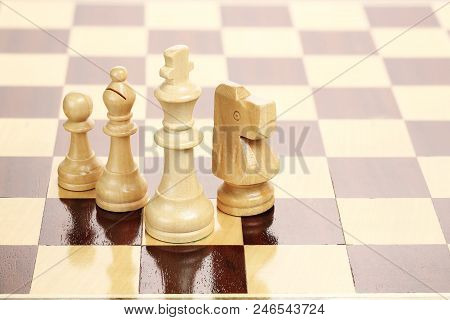 Wooden King, Knight, Bishop And Pawn On Chessboard