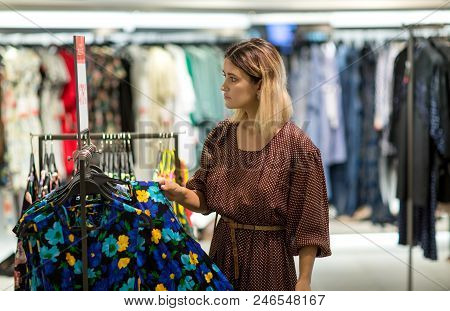 Young Woman Choosing Clothes In Mall Or Clothing Store - Shopping, Fashion, Style And People Consume