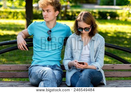 A Guy With A Girl In The Summer In A Park In Nature. They Sit On A Bench. In The Hands Of A Smartpho