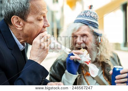 Nice refugee. Caring businessman spending his break time with nice kind-hearted starving refugee while eating burger together poster